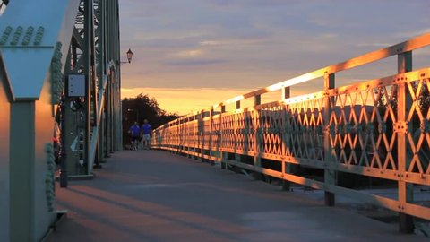 Two people walking slowly on Mária Valéria Bridge in Hungary, Europe. The sun is slowly setting.