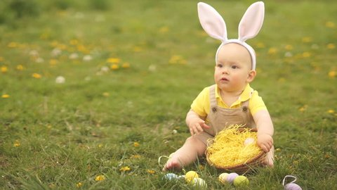 Baby first sees Easter eggs. He holds in his hand and shouts from happiness sitting on the grass in the park. Happy easter family
