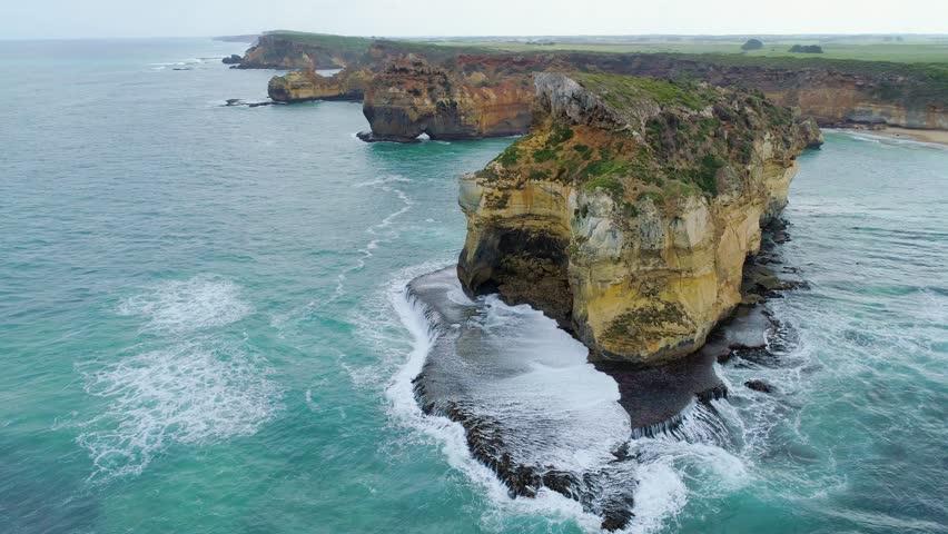 Static aerial shot of sea waves breaking over huge rock formations