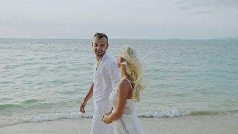 Couple walking on beach. Young happy interracial couple walking on beach smiling holding around each other - slow motion.