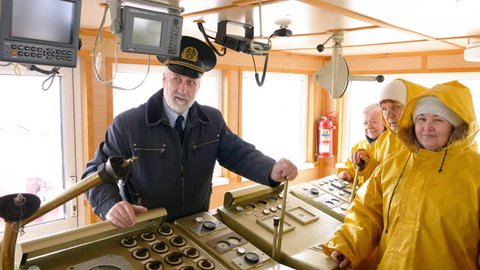Elderly grey-haired captain of the Norway ship in the wheelhouse is talking with his team of sailors and workers in yellow raincoats and gives them instuctions.