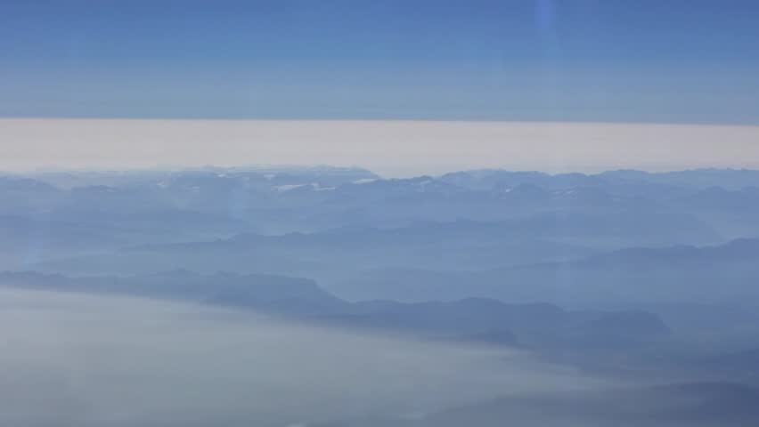Beautiful view over mountains and clouds from above, as seen through airplane window. Passenger POV traveling by air. Traveler in cabin at plane wing in flight trip