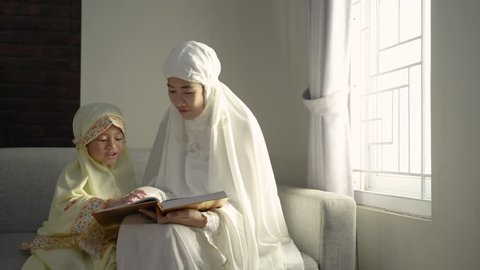 muslim parent and daughter reading quran after praying together