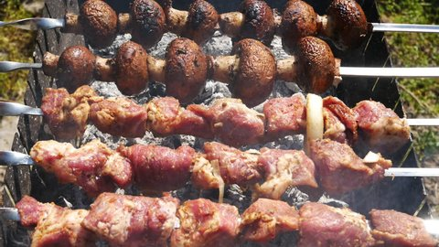 Meat and mushrooms are fried on coals.Preparing tasty meat barbeque on skewers. This is a shish-kebab. Shish-kebab - a popular dish of Caucasian, Turkish and Asian cuisine. Close up