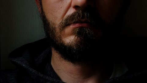 Don't speak, be quiet - close up portrait of bearded man on the door saying shhh. Finger on lips. Head and shoulders, no eyes. Danger. Violence concept.