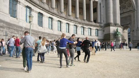 Brussels, Belgium - April 1, 2019:Wonderful view of happy young people dancing outdoors at a high traditional building with columns on a sunny day in spring in slow motion