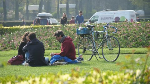 Brussels, Belgium - April 1, 2019:Optimistic view of three young people sitting and having a picnic on green lawn with walking people nearby in Brussels on sunny day in slo-mo
