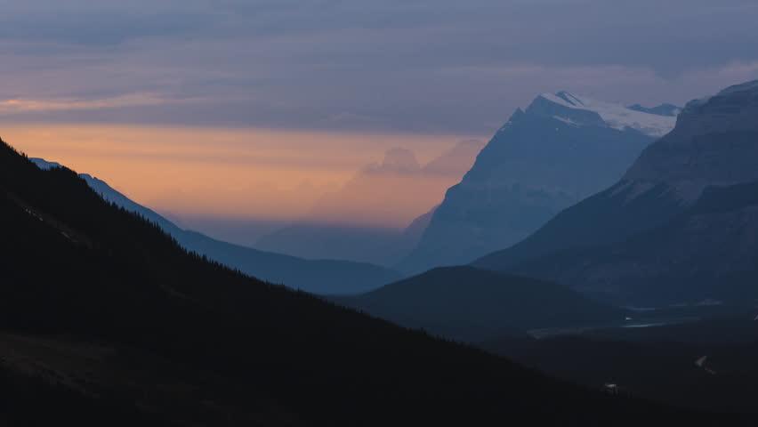 Light beams illuminating moutain peaks at sunset in valley 4K