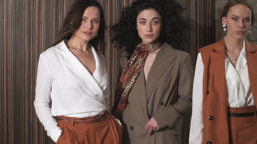 HD Footage. Slowmo. Three beautiful young girls in business suits. Business style. Posing at a photo shoot in the studio. #1029365402