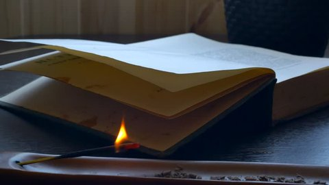 On the table there is an old book and an apical wand that burns after it fades and begins to smoke....
