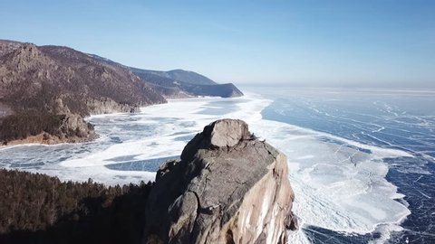 Aerial Perspective View of Beautiful Deep Blue Ice Textured Frozen Baikal Lake Surface and Coast from above Captured with a Drone at Sunny Winter Day in Russia