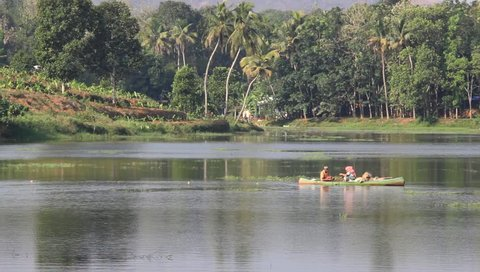 Thattekad, Kerala, India - February 25, 2019: Unidentified local fishing couple in country boat retrieve trap net laid for catching fish in the backwaters of Periyar River in Thattekad, India
