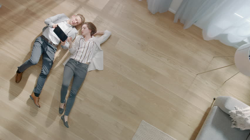 Young Couple are Lying on a Wooden Flooring in an Apartment. They are Using a Tablet Computer. Cozy Living Room with Modern Interior, Grey Sofa and Wooden Parquet. Top View Camera Footage. | Shutterstock HD Video #1029383852