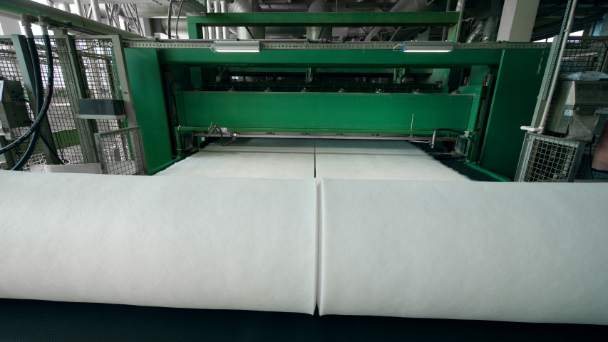 Plant conveyor coils synthetic fabric into big rolls. | Shutterstock HD Video #1029399302