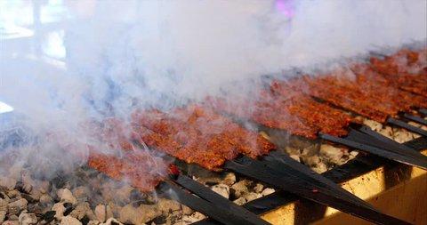 Kebab or kebap meat shish on metal skewer barbecue and embers in the kebab restaurant. Skewering bbq Kebab. Traditional Turkish Adana Kebab