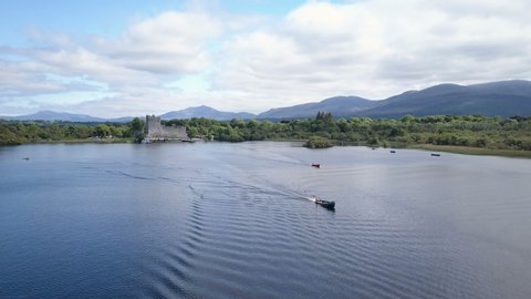 Low altitude pass over small pleasure craft as they depart from shore along a glass like lake.Location Ross Castle, Ring of Kerry, Killarney, ireland,a destination along the Wild Atlantic Way