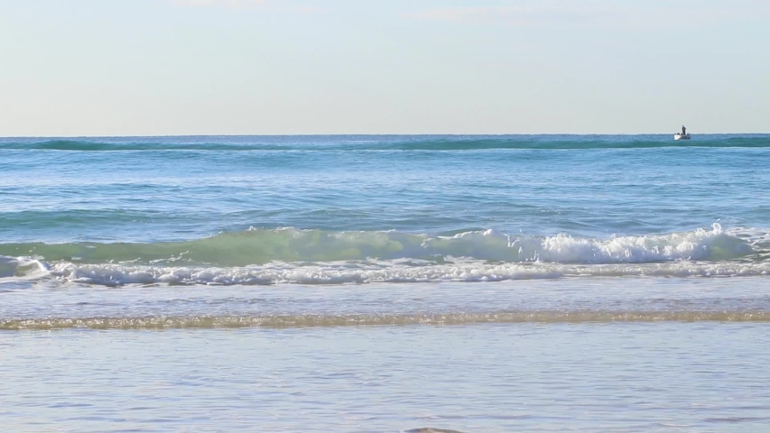 Blue turquoise waves with white was crashing onto the shoreline of a orange white sandy beach along the Gold Coast, Australia coastline at sunrise with blue orange skies and crystal clear blue water | Shutterstock HD Video #1029489212