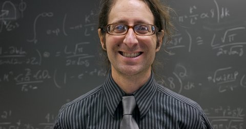 Happy smiling professor, scientist, or math genius looking directly at the camera standing in front of a blackboard