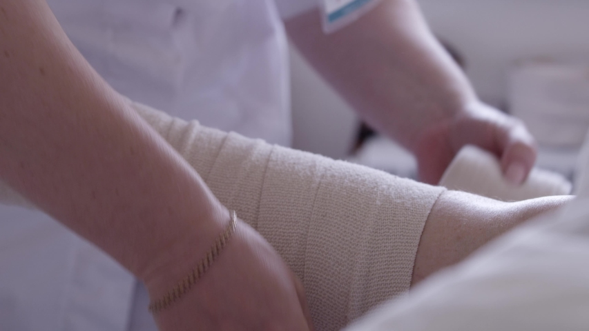 Nurse bandages a patient's leg with an elastic bandage in a hospital bed | Shutterstock HD Video #1029509822