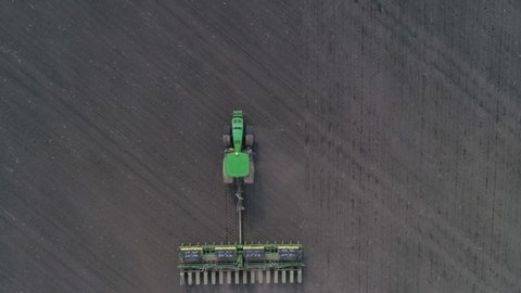 KHERSON, UKRAINE - APRIL 15, 2019: tractor cultivating arable land for seeding crops, aerial view on modern agriculture machinery at field in spring