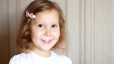 Baby girl drinking a milk drink from a bottle, kefir, dairy product. Child smiling and showing a white mustache from yogurt.