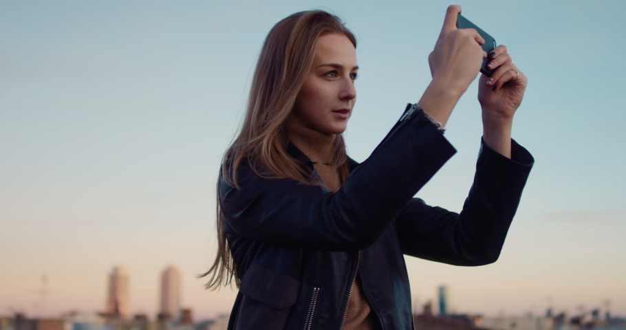 Young beautiful tourist girl with her smartphone taking a picture on the rooftop terrace with sunset views of an old town. Slow Motion. Shot on RED digital cinema camera   Shutterstock HD Video #1029670682