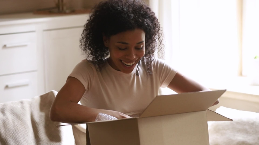 Happy satisfied african american woman customer receive carton box open delivered parcel excited with good purchase shipping, smiling black consumer get post package look inside sit on sofa at home