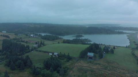 Cinematic drone / aerial footage rotating showing some hills, farms, the ocean and some chalets in Kingsburg, Nova Scotia, Canada during summer season.