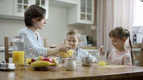 mother put cornflakes from bowl on the plate with a spoon to her son while daughter eating