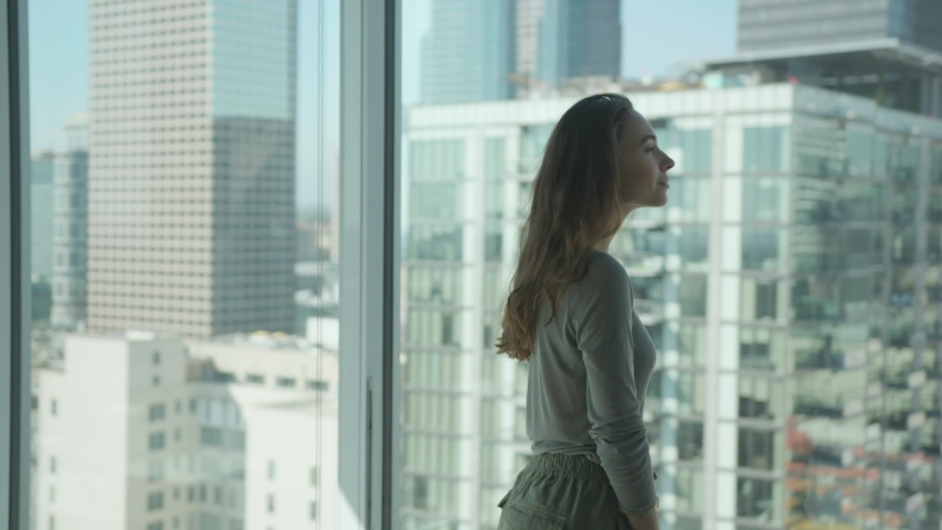 Woman standing against floor to ceiling windows with amazing city view. Los Angeles downtown. Inspiration  | Shutterstock HD Video #1029744542
