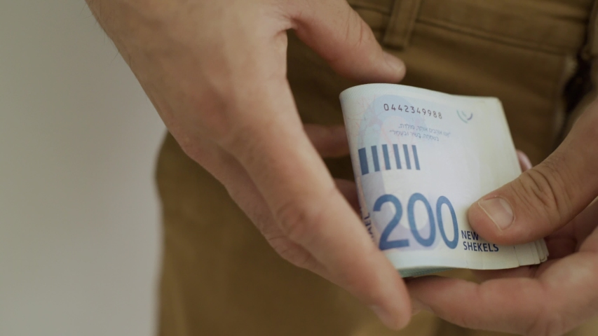 Man counts Israeli bills and puts them inside his pocket | Shutterstock HD Video #1029758132