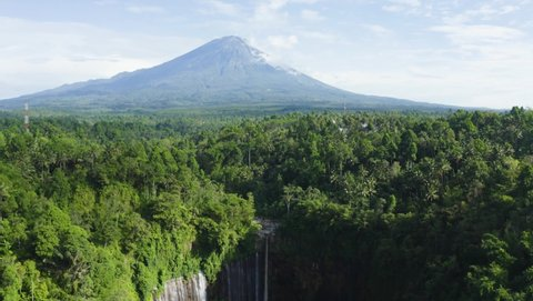 Beautiful aerial view of Coban Sewu waterfall with Mount Semeru background and tropical forest in Lumajang, East Java, Indonesia. Shot in 4k resolution from a drone flying forwards