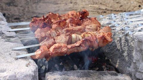 Shish kebab is fried on a brazier. Barbecue meat. Pork shashlik. Video skewers on skewers fried. Juicy meat