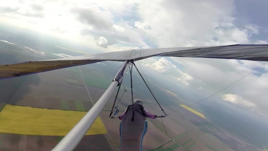 Hang glider pilot race between clouds on high altitude. Beauty of extreme sport | Shutterstock HD Video #1029825392