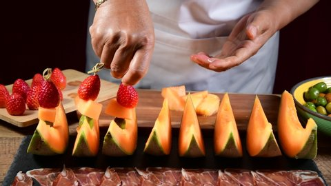 Woman decorating a blackboard with ham and melon with a skewer of strawberries, melon and olives