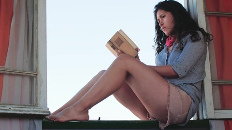 Hispanic girl reading a book sitting on the windowsill. 4k