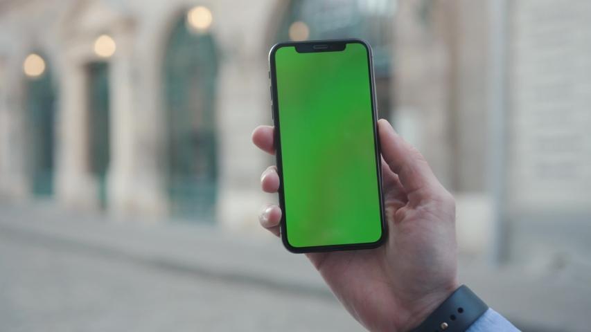 NEW YORK - April 5, 2018: Man hands young man holding a smartphone with vertical green screen background sun city touchscreen wireless business evening cellphone communication device digital internet | Shutterstock HD Video #1029886412