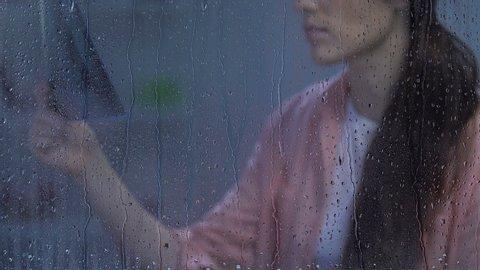 Hopeless sick female looking at lungs x-ray near rainy window, suffering TB