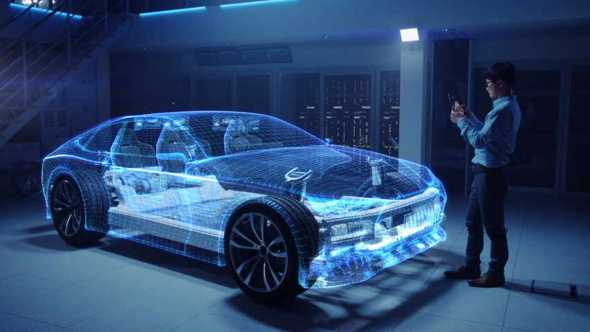 Automotive Engineer Working on Electric Car Chassis Platform, Using Tablet Computer with Augmented Reality 3D Software. Innovative Facility: Vehicle Frame with Wheels Becomes a Solid Virtual Model.