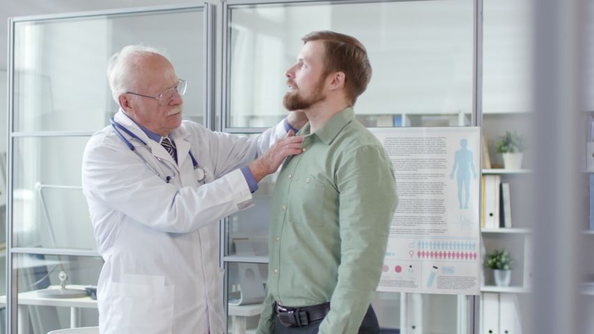 Professional senior doctor in white coat presses outside of neck and throat of male patient while checking his lymph nodes during clinical checkup | Shutterstock HD Video #1029938192