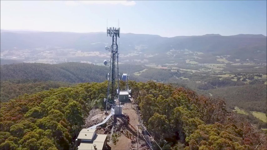 AERIAL: A cell phone tower overlooking it's coverage area   Shutterstock HD Video #1029990932