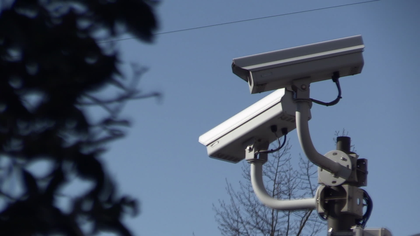 Close up of a surveillance camera against blue sky, watching everye | Shutterstock HD Video #1030030292