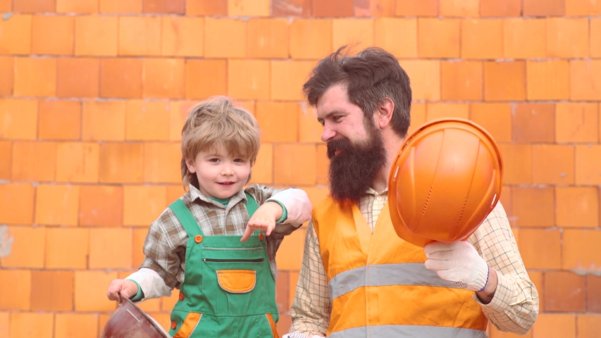 Future worker son with father. Happy family building a house. Work with tools. Childhood concept. Concept of partnership. Toddler boy in an orange helmet or helmet helps his bearded father   Shutterstock HD Video #1030042262