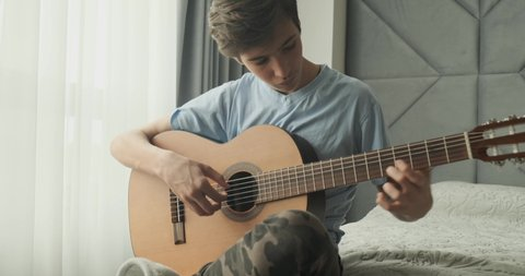 Young man playing on acoustic guitar, at home. Teenage boy with a wooden guitar sits on a sofa.  Child playing guitar.  Teen guy plays on a classical guitar. Real time footage.