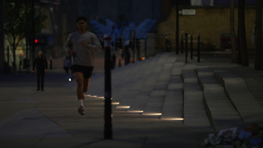 Asian male running through the city at night, in slow motion   Shutterstock HD Video #1030075772