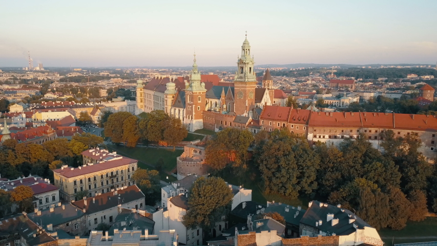 Aerial view of Royal Wawel Cathedral and castle in Krakow, Poland, with Vistula river, park, yard and tourists at sunset. Old city in the background | Shutterstock HD Video #1030096442