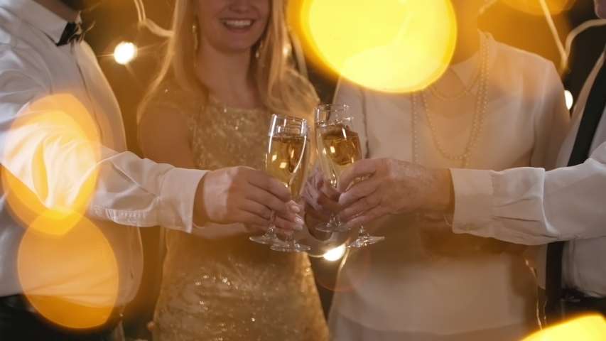 Mid-section shot with bokeh effect: unrecognizable man and woman smiling and clinking glasses of champagne with elderly couple in room decorated with fairy lights   Shutterstock HD Video #1030111142