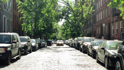 NEW YORK - MAY 21, 2019: cobblestone treelined street on bright sunny day West Village New York City NYC.