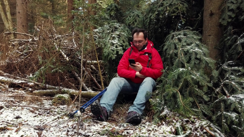 Middle age male hiker relaxing in winter wood, checking route in smartphone | Shutterstock HD Video #1030194062