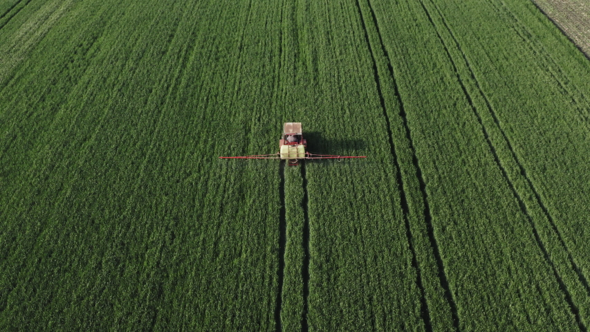 Tractor spraying pesticides on an agricultural field #1030197182